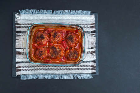 Meatballs baked in form in the oven with a gravy of tomato paste, tomatoes, onions and spices. flat lay