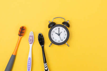 toothbrush and alarm clock time to brush your teeth before going to bed, in the morning on a yellow background.