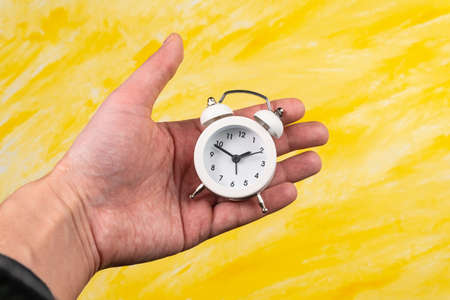 white alarm clock in hand on yellow background. copy space. flat lay