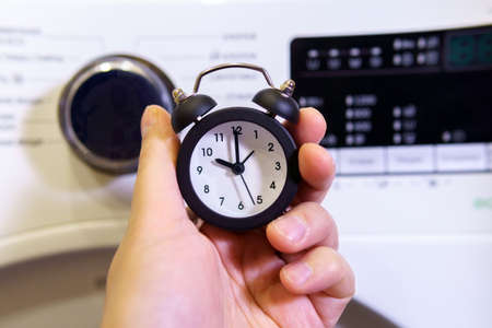 Washing clothes. Time to wash your dirty laundry. alarm clock in hand selective focus