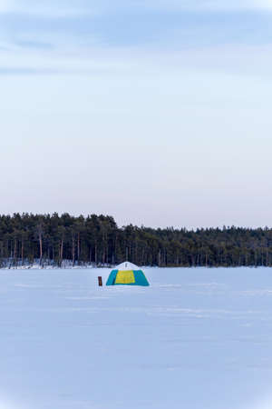 winter tent on the lake for fishing. winter sports vertical photo