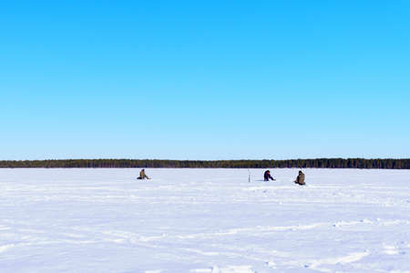 fishermen sit fishing on a winter lake against a background of forest and blue sky. sports winter fishing