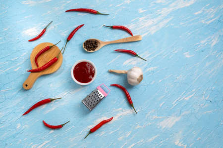 ingredients for chili sauce, chili pepper, garlic, sea salt. top view on a blue background Archivio Fotografico
