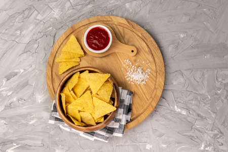 Tortilla or Nacho Chips for snack. Corn Chips Nachos on grey background, top view Archivio Fotografico