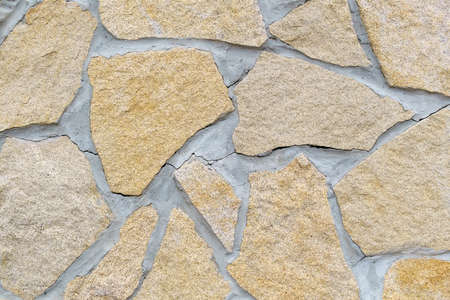 shaped stone wall creation, in various shades of brown. wallpaper. texture background