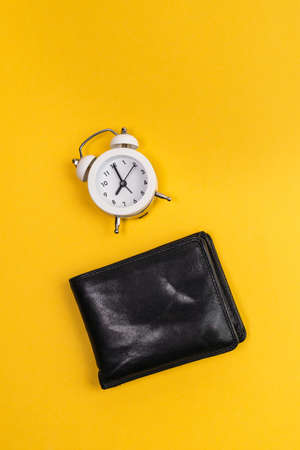 alarm clock and wallet yellow background. Time is money concept. vertical photo