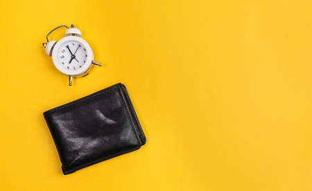 alarm clock and wallet yellow background. Time is money concept. copy space Archivio Fotografico
