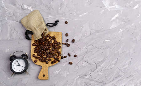 coffee bean alarm clock. buying coffee beans. on a gray concrete background