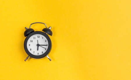 black alarm clock on yellow background. copy space. flat lay Archivio Fotografico