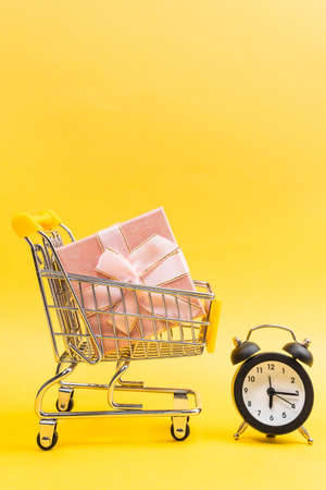 shopping cart, gift shopping time concept on yellow background. vertical photo
