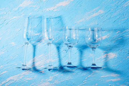 empty drinking glasses on a light blue background. hard shadows top view