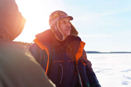 Portrait of a brutal man dressed in winter clothes, on a winter lake. ice fishing Archivio Fotografico