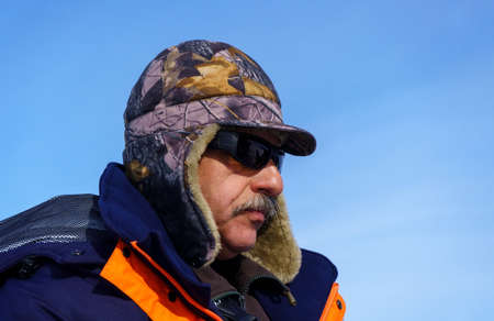 portrait of an adult man in a hat and sunglasses. in winter. winter time. against the blue sky