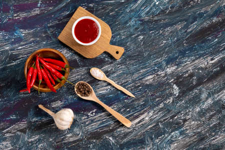 ingredients for chili sauce, chili pepper, garlic, sea salt. on a black background. copy space