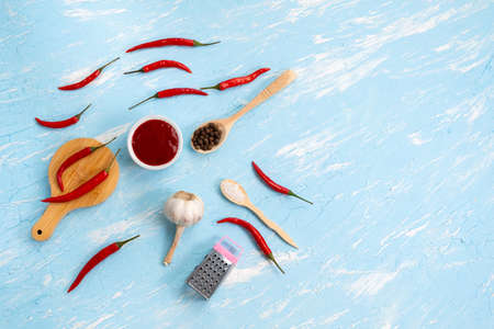 chili sauce, chili pepper, garlic on a blue background. Spicy food, Mexican cuisine. copy space