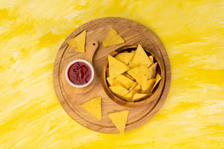 Tortilla or Nacho Chips for snack. Corn Chips Nachos on yellow background, top view