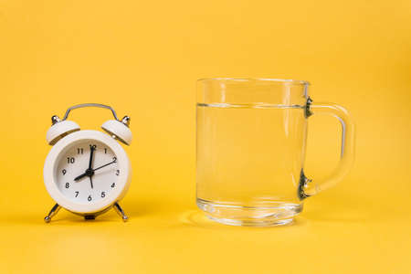 Alarm clock and a glass of water on a yellow background. Wake up early in the morning. Drink water