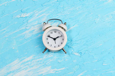 alarm clock on a blue background. copy space. flat lay