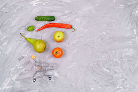 buying healthy vegetables and fruits concept on gray background top view. copyspace