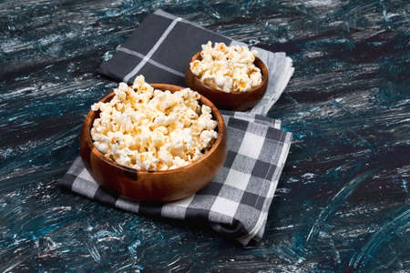 Tasty salted popcorn in bowl on dark background. Top view with copy space. flat lay