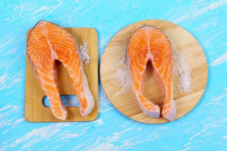 raw salmon, sea salt blue table, top view. Preparation for cooking fish food. Salmon steak.