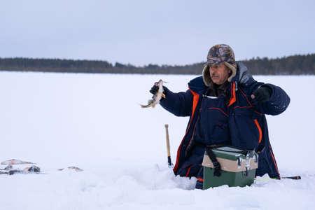 ice fishing. fisherman fishing on frozen lake. Winter frosty morning fishing on river. Archivio Fotografico