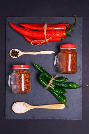 Red and green chili peppers. Hot spicy food ingredient. Dark slate background power supply.