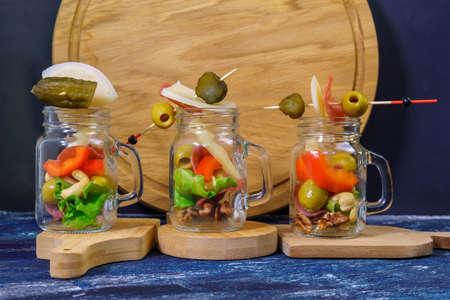 Glass jar jarcuterie nuts, olives, cheese, meat chips, salad. Healthy good carbs and fats, a light snack.