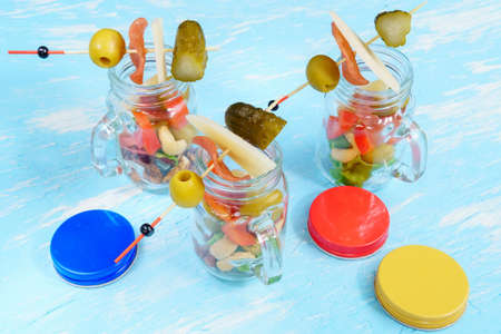 Jarcuterie Snacks in transparent jars cheese ham olives lettuce cucumbers nuts. Stok Fotoğraf