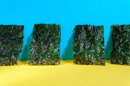 Crispy dried seaweed, Nori chips piece of roasted seaweed sheet on a colorful background. Healthy food concept.