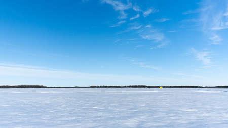 Winter landscape on a frozen lake, forest, flying clouds in a blue sky. Stok Fotoğraf