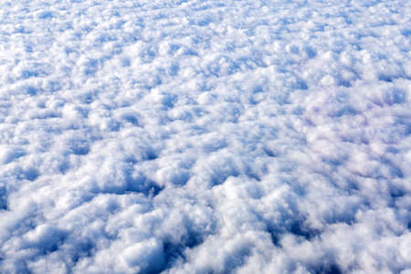 Blue sky with white clouds background with copy space for text, sky wallpaper. View from the plane window