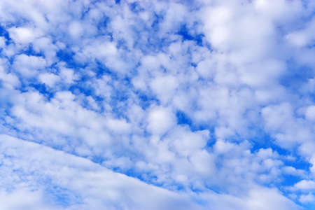 Clouds sky background with white volumetric foamy clouds in the blue sky. Many cumulus clouds. Background. copy space for text
