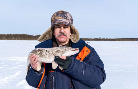 Winter fishing, fisherman holds trophy pike Esox lucius. space for copying text Stok Fotoğraf