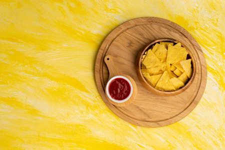 Tortilla or Nacho Chips for snack. Corn Chips Nachos on yellow background, top view, copy space.