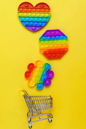 Colorful antistress sensory toy fidget push pop it. On a yellow background. Vertical photo