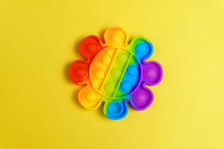 Colorful antistress sensory toy fidget push pop it. On a yellow background Stok Fotoğraf