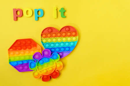 Pop it toy silicone colorful antistress on yellow background. Copy space. Top view