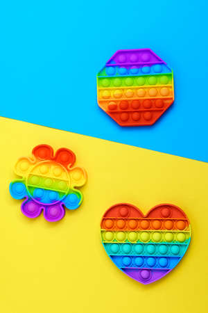 Rainbow color pop it toy. Anti stress for adults and children. Multicolored blue yellow background Stok Fotoğraf