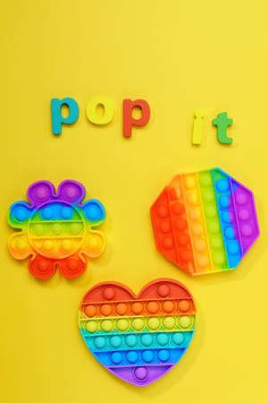 Pop it fidget sensory toy on a yellow background. Top view Stok Fotoğraf
