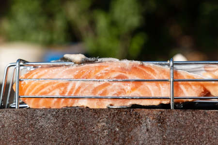 Cooking salmon steak close-up on an outdoor barbecue grill. Selective focus Banque d'images