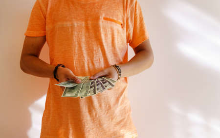 A young tanned man holds money dollars in his hands. Space for copying text