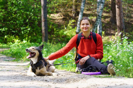 A happy girl is playing with her dog. Love between a person and an animal.