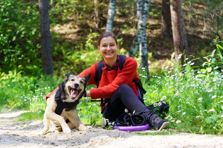 Girl with petting a dog. Girl walks with a pet through the forest. Banque d'images