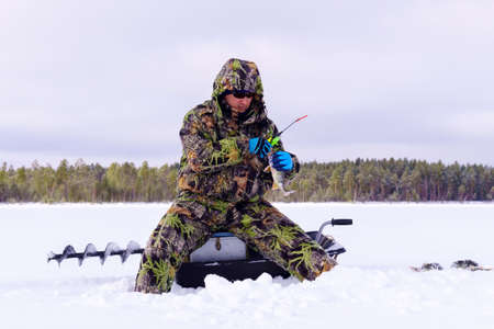 A fisherman in special clothes catches fish in winter on the lake. The concept of survival in the wild in winter Banque d'images