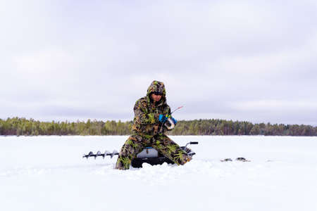 Ice fisherman on the lake catches perch during winter fishing. Space for copying text