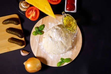 Ingredients for making pizza. Dough cheese, onions, tomatoes, olive oil cucumbers ketchup. Black background Banque d'images