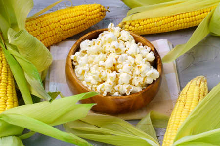 Tasty traditional popcorn and corn cobs on grey background Banque d'images