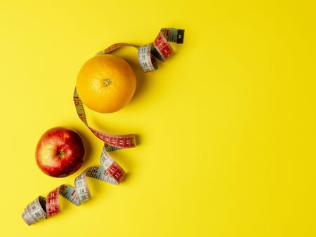The concept of proper nutrition. Juicy fruit, Apple and orange wrapped measuring tape on a bright yellow background. Top view, copy space 写真素材