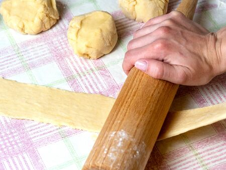 the Baker rolls the dough into strips on the kitchen table, sprinkled with flour. Stock Photo